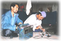 men repairing radio equipment in Shimshal, Pakistan